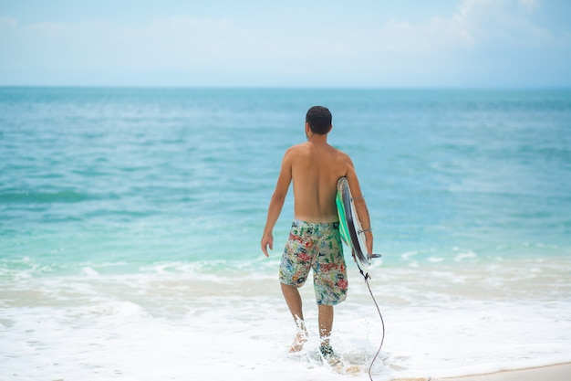 Surfer. człowiek surfing z deską surfingową, chodzenie na piaszczystej plaży tropikalnej.