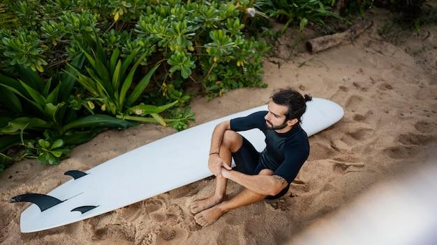 Surfer i jego wysoki widok na deskę surfingową