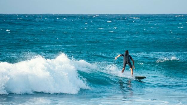 Surfer jazda fala w świetle dziennym długi widok
