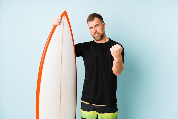 Surfer mężczyzna na białym tle na niebieskiej ścianie pokazano pięść, agresywny wyraz twarzy.