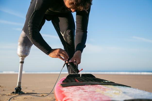 Surfer mężczyzna ubrany w piankę i sztuczną kończynę, przywiązujący deskę surfingową do kostki na piasku