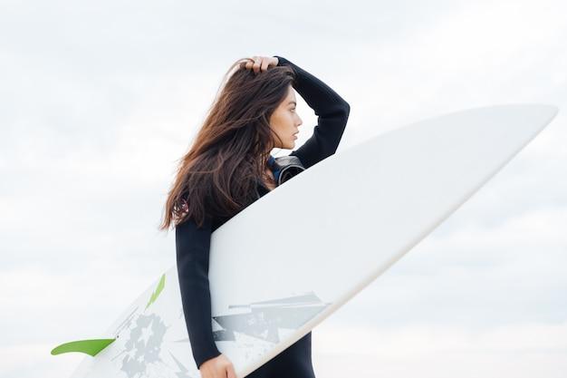 Surfer młoda dziewczyna z seksownym dopasowanym ciałem w stroju kąpielowym, trzymając deskę surfingową