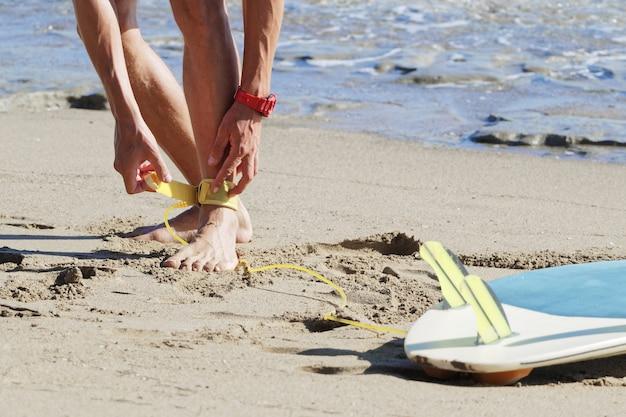 Surfer mocujący do kostki żółtą smycz do deski surfingowej.