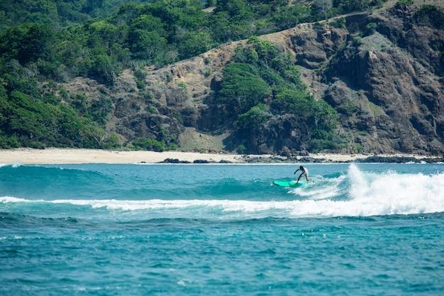Surfer na błękitnej fali.