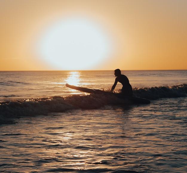Surfer przygotowuje się do surfowania po morzu o zachodzie słońca