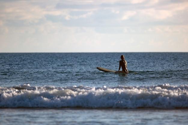 Surfer siedzący w oceanie o zachodzie słońca
