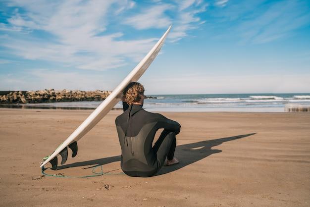 Surfer siedzi na piaszczystej plaży i obok deski surfingowej.