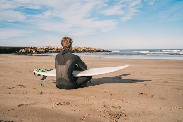 Surfer siedzi na piaszczystej plaży z deską surfingową