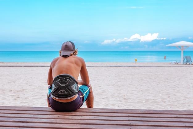 Surfer siedzi na tarasie na plaży i patrzy w dal,