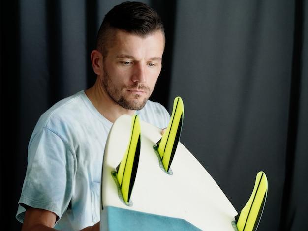 Surfer sprawdza deskę surfingową w domu.