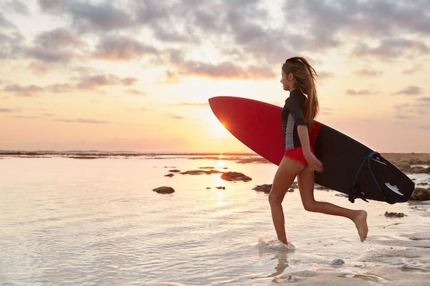 Surfer w ruchu. aktywna atletyczna szczupła kobieta wpada do wody spokojnego oceanu