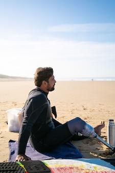 Surfer w średnim wieku ze sztuczną nogą, siedzący na plaży i patrząc na morze
