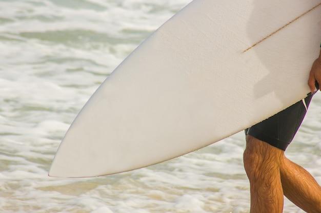 Surfer z deską surfingową w kierunku morza na plaży barra da tijuca w rio de janeiro.