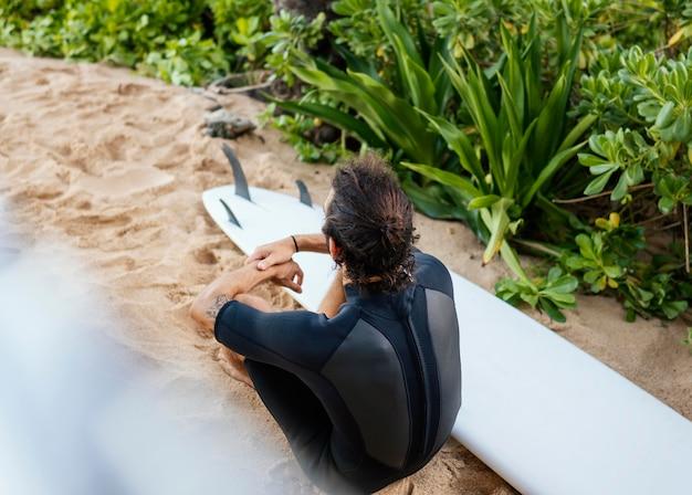 Surfer z wysokim widokiem i jego deska surfingowa