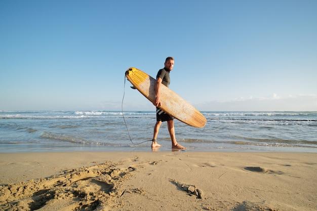 Surfer z żółtą deską surfingową idzie rano do oceanu