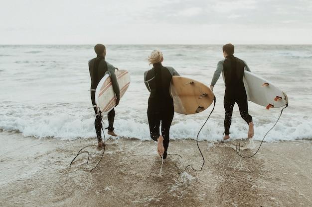 Surferzy biegnący w stronę morza