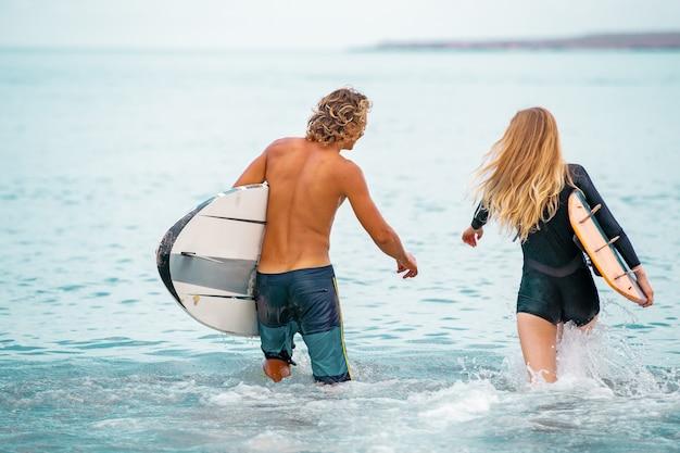 Surferzy na plaży - uśmiechnięta para surferów spacerująca po plaży i bawiące się latem