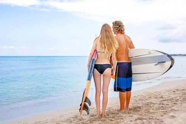 Surferzy na plaży - uśmiechnięta para surferów spacerujących po plaży i dobrze się bawiących latem. pojęcie sportu ekstremalnego i wakacji