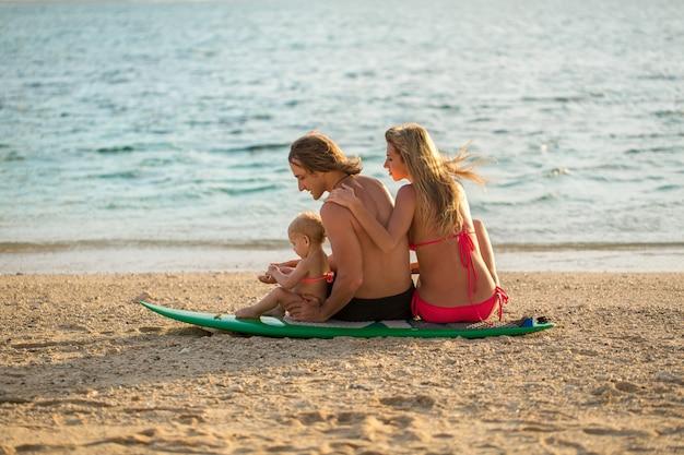 Surfing. szczęśliwa rodzina siedzi na desce surfingowej. pojęcie o rodzinie, sporcie i zabawie