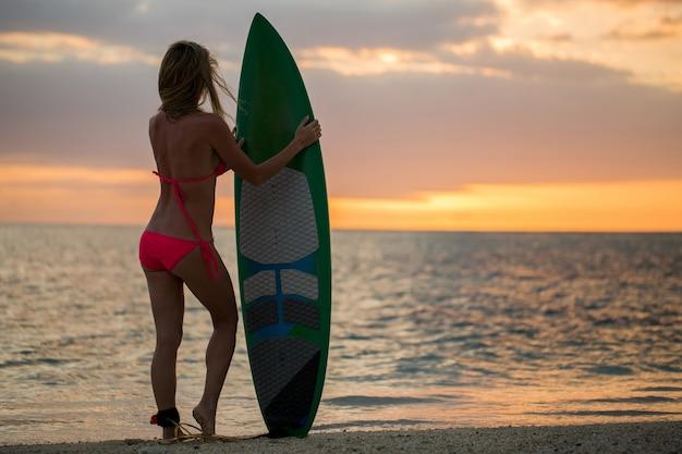 Surfingowiec surfingowiec dziewczyna patrzeje ocean plaży zmierzch.