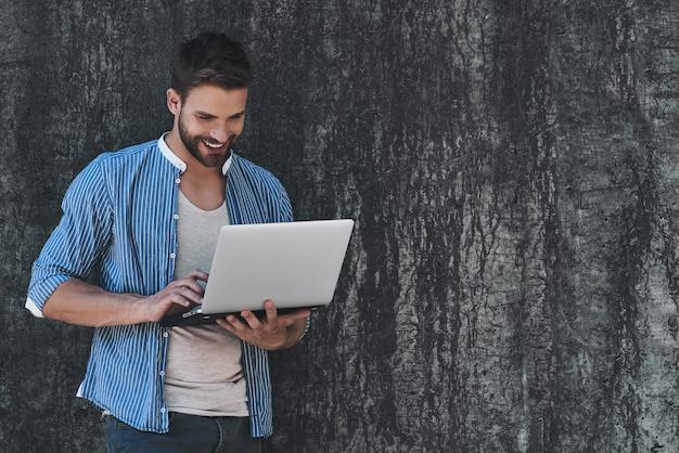 Surfowanie po sieci na zewnątrz przystojny młody mężczyzna w eleganckim stroju casual pracuje na laptopie, podczas gdy