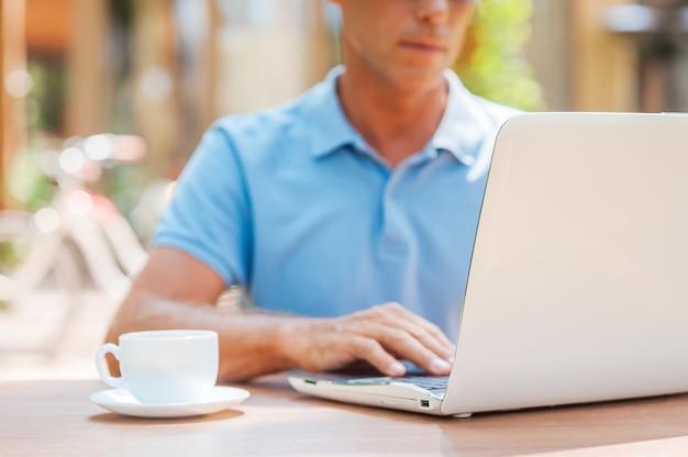 Surfowanie po sieci w kawiarni. zbliżenie: pewny siebie dojrzały mężczyzna pisze coś w swoim notesie i uśmiecha się siedząc przy stole na zewnątrz z domem w tle