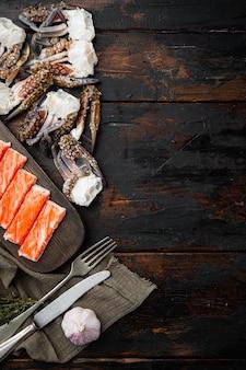 Surimi świeżego mięsa kraba z niebieskim zestawem krabów pływackich, na ciemnym drewnianym tle, widok z góry płasko leżący, z copyspace i miejscem na tekst