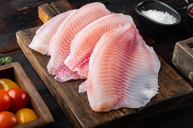 Surowa biała ryba tilapia, z ryżem basmati i składnikami z pomidorów koktajlowych, na ciemnym drewnianym tle