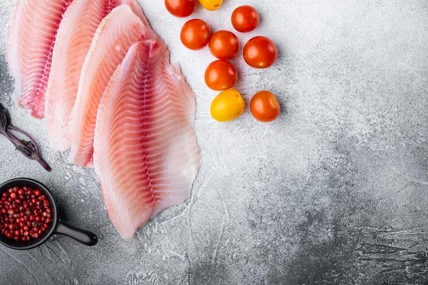 Surowa biała ryba tilapia, ze składnikami ryżu basmati i pomidorkami koktajlowymi, na szarym tle, widok z góry z miejscem na tekst