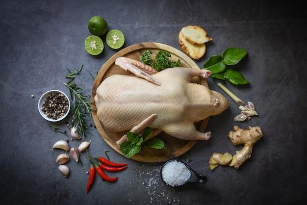 Surowa cała kaczka z przyprawami ziołowymi do gotowania na ciemnym palcie, świeże mięso kaczki na drewnianej tacy do jedzenia