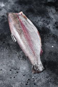 Surowa cała ryba pstrąg bez głowy. czarna powierzchnia. widok z góry