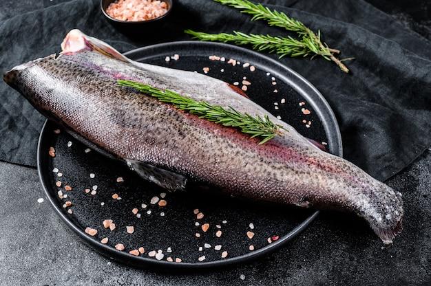 Surowa cała ryba pstrąg bez głowy, z solą i rozmarynem. czarna powierzchnia. widok z góry