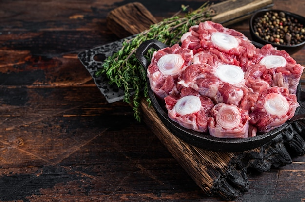 Surowa cielęcina wołowina ogon wołowy mięso na deska drewniana rzeźnika z tasakiem. ciemne drewniane tło. widok z góry. skopiuj miejsce.