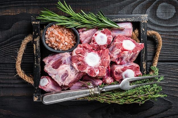 Surowa cielęcina wołowina ogon wołowy mięso w drewnianej tacy z tymiankiem. czarne drewniane tło. widok z góry.
