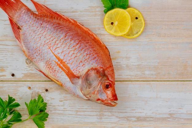 Surowa czerwona ryba tilapia z ziołami i cytryną i limonką na drewnianym stole. widok z góry, miejsce na kopię.