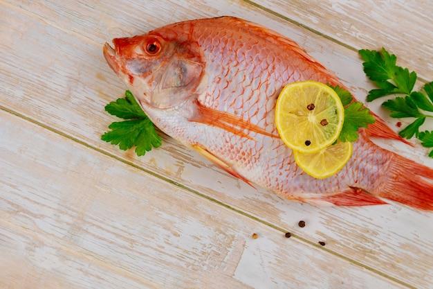 Surowa czerwona ryba tilapia z ziołami i cytryną i wapnem na podłoże drewniane. widok z góry, miejsce na kopię.