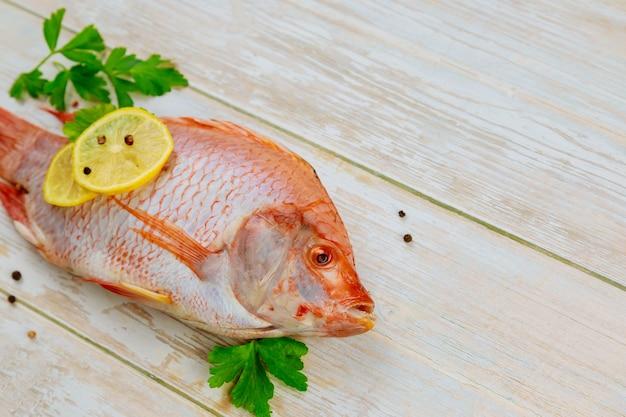 Surowa czerwona ryba tilapia z ziołami i cytryną na drewnianym
