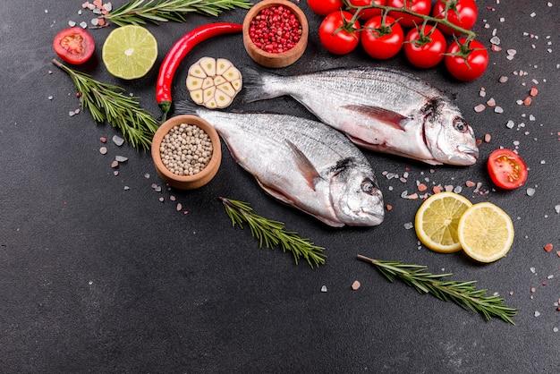 Surowa dorado ryba z pikantność gotuje na tnącej desce. dorado ze świeżych ryb. dorado i składniki do gotowania na stole