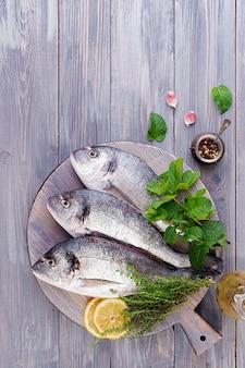 Surowa dorado ryba z zielarskimi ziele gotuje na tnącej desce. widok z góry