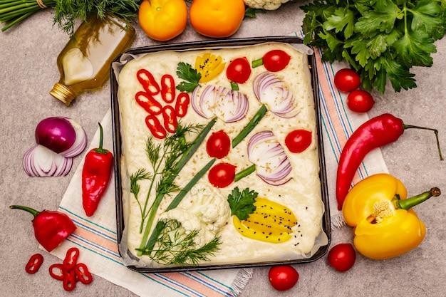 Surowa focaccia ogrodowa. świeże ciasto i warzywa, oliwa z oliwek, warzywa