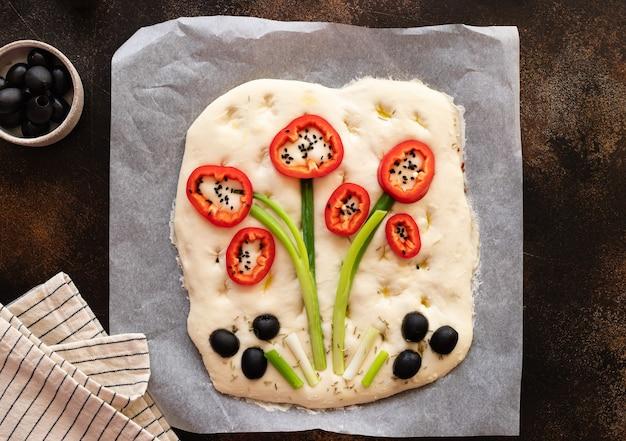 Surowa focaccia ozdobiona warzywami na pergaminie gotowa do pieczenia art focaccia