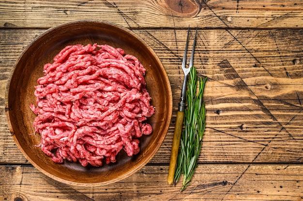 Surowa jagnięcina mielona, mielone mięso baranie z ziołami na talerzu. drewniane tło. widok z góry. skopiuj miejsce.