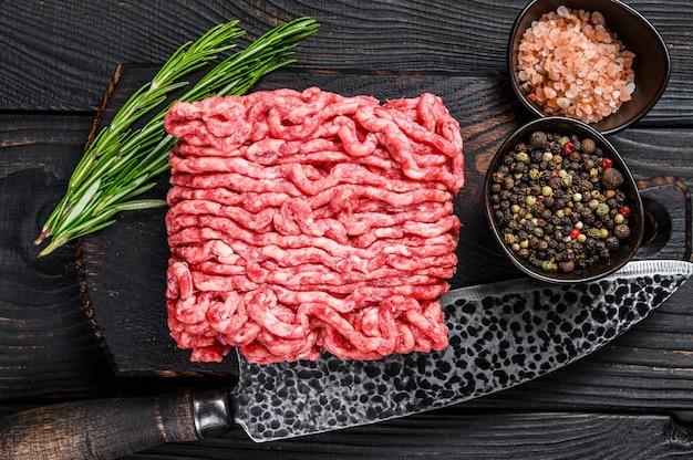 Surowa jagnięcina mielona, mięso mielone z ziołami i przyprawami na drewnianej desce do krojenia. czarne drewniane tło. widok z góry.
