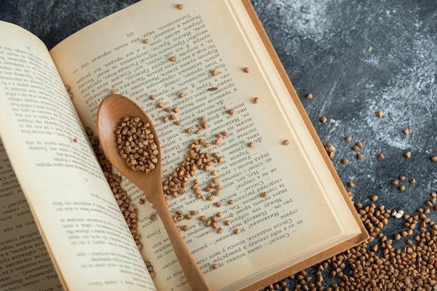 Surowa kasza gryczana rozrzucona na otwartej książce