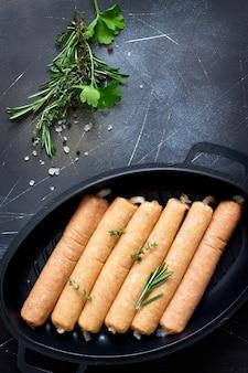 Surowa kiełbasa na żeliwnej patelni grillowej z ziołami i przyprawami na ciemnym kamiennym tle piknik