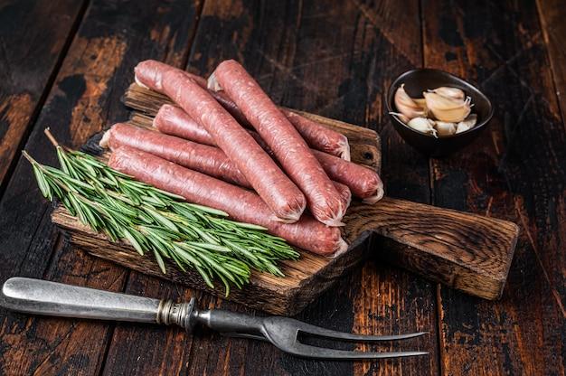 Surowa kiełbasa wołowa i wieprzowa na starej desce do krojenia z widelcem do mięsa vintage. ciemne drewniane tło. widok z góry.