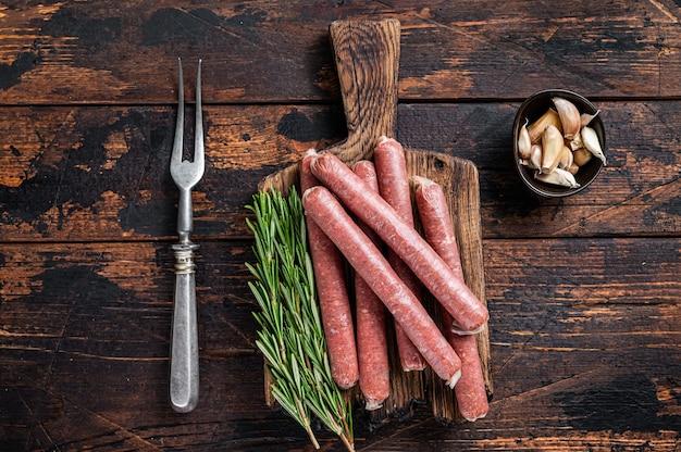Surowa kiełbasa wołowo-wieprzowa na starej desce do krojenia z rocznika widelcem do mięsa.