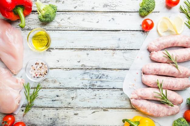 Surowa kiełbasa z kurczaka domowej roboty z przyprawami i warzywami na białym drewnianym