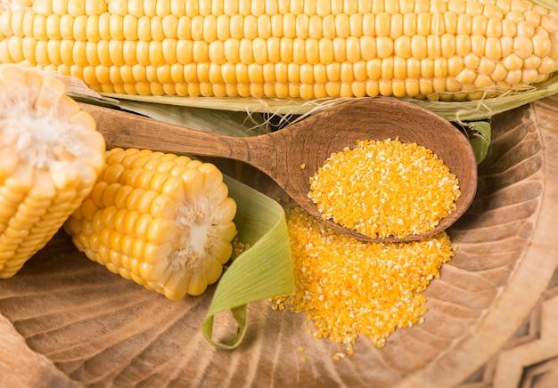 Surowa kukurydza z zielonymi liśćmi na białym tle.