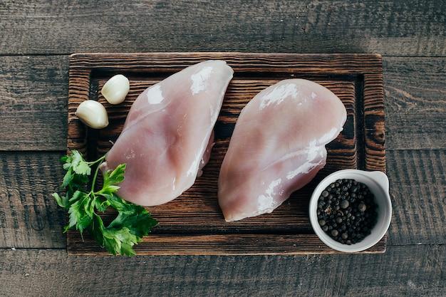 Surowa kurczak pierś przepasuje na brown drewnianej desce na stołowym tle